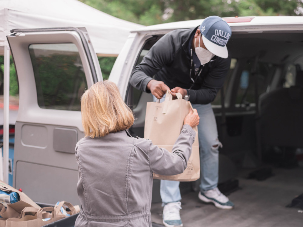 Person handing a bag of groceries from a van to another person